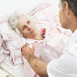 Male nurse sitting at old woman's bed side
